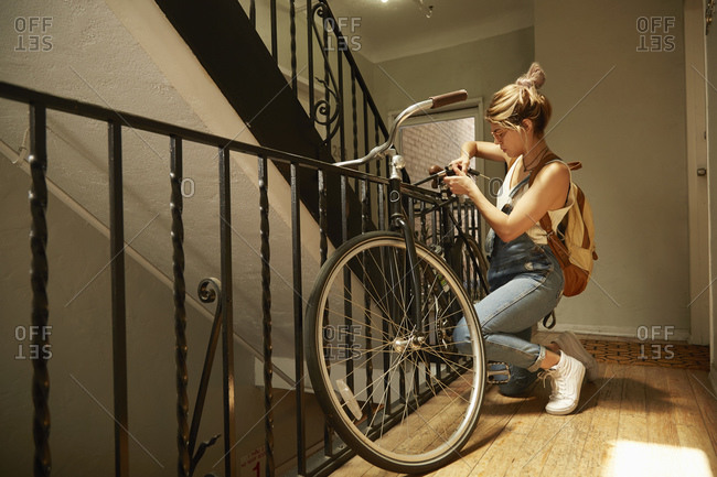 Woman unlocking bike parked in an apartment stairway