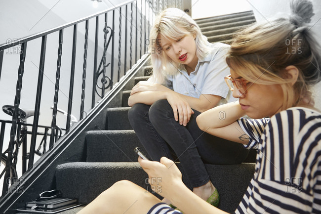 Two young women sitting on steps while looking at a cell phone