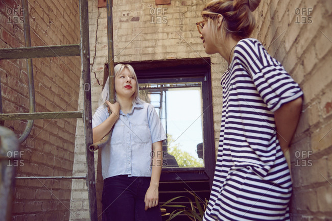 Two young women hanging out by a fire escape