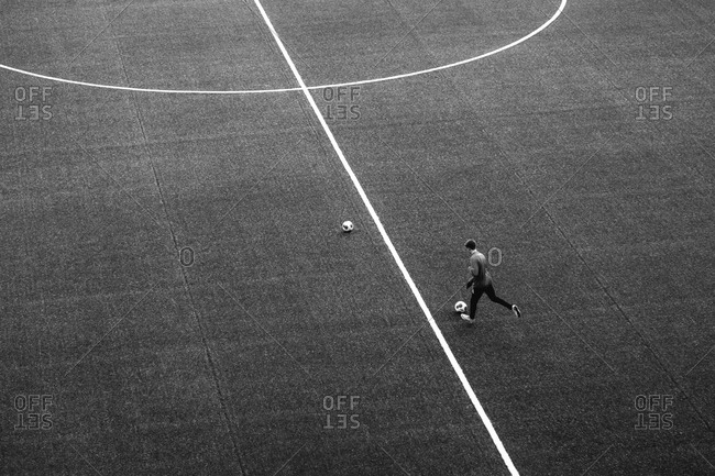 Overhead view of a man kicking a soccer ball on a soccer field