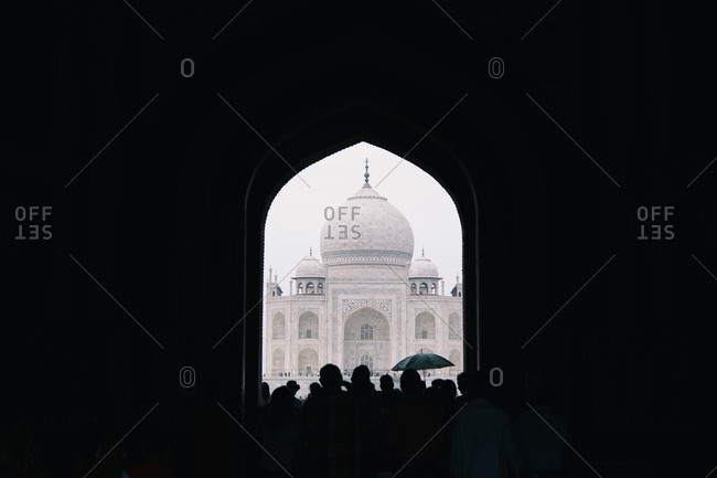 Silhouette of a group of people standing near the Taj Mahal in the city of Agra, India