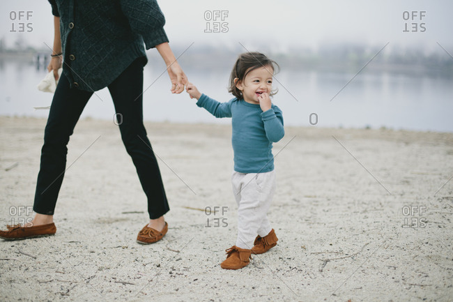 Mother holding daughter's hand while walking on a beach