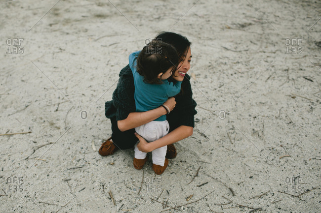 Daughter hugging mother on a beach