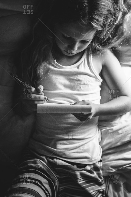 Little girl writing with pen and paper in black and white