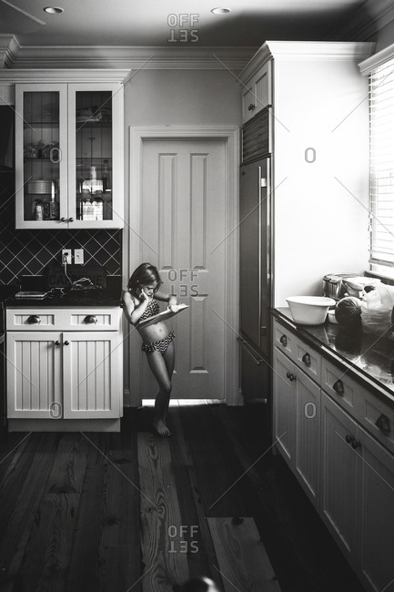 Little girl standing in the kitchen reading a book in her swimsuit