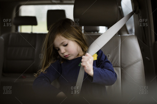 Child buckling her seatbelt in a vehicle