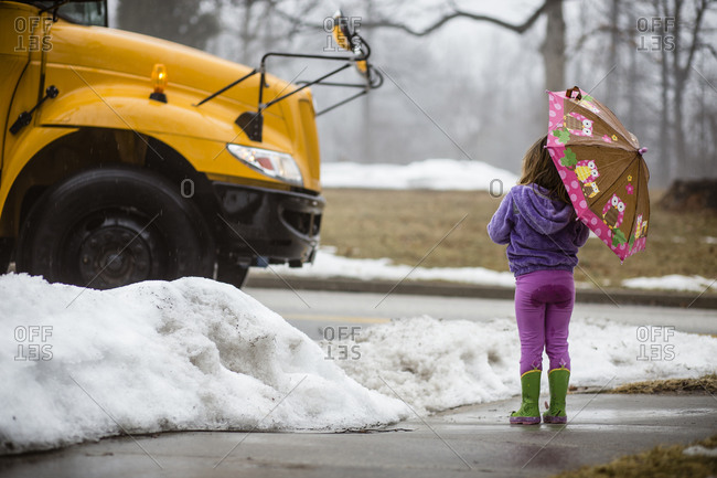 Little girl with an umbrella waiting for the school bus