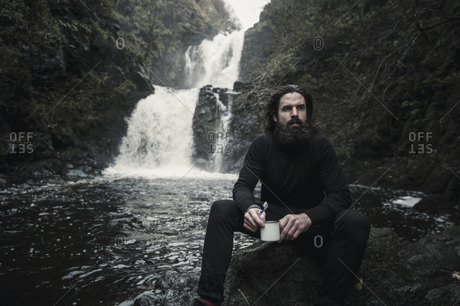A man sitting holding a mug, by a fast flowing stream and cascading water