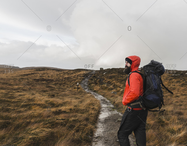 A man in winter clothing in open countryside by a path