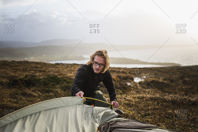A man feeding a tent pole into the tent fabric