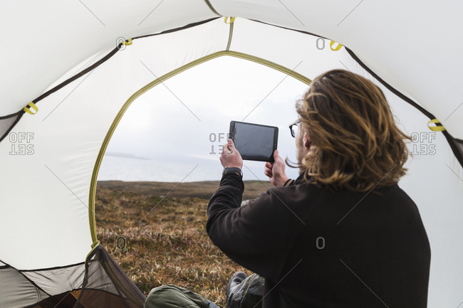 A man taking a photograph with a digital tablet while camping