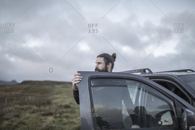 A man standing by an open car door, looking around him, under a cloudy wintery sky
