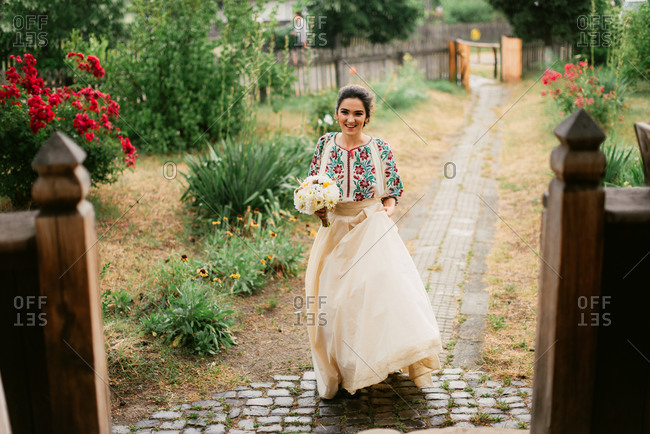 Bride in traditional Romanian embroidered blouse walking on garden path
