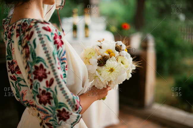 Close-up of bride in Romanian embroidered blouse holding her wedding bouquet