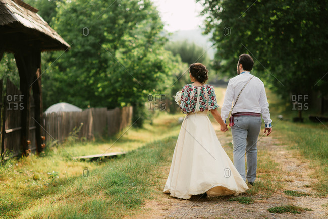Back view of bride and groom in traditional Romanian folk dress walking in farm