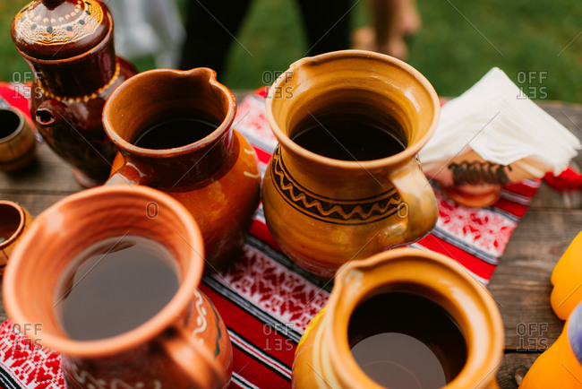 Pottery pitchers filled with drink at outdoor celebration