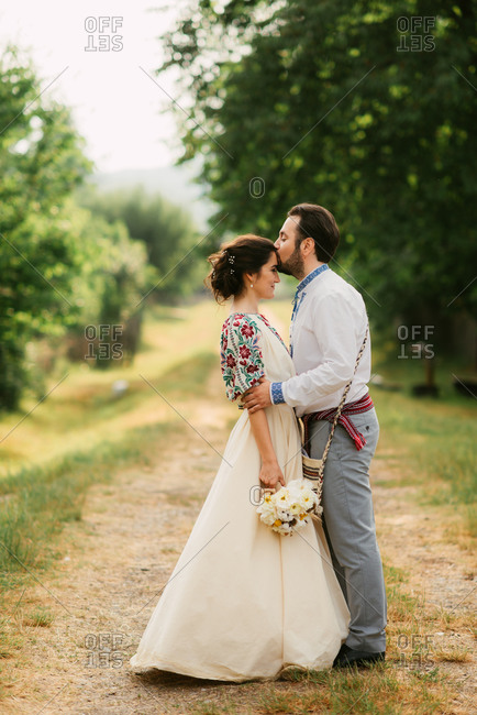 Portrait of bride and groom kissing at traditional folk wedding on Romanian farm
