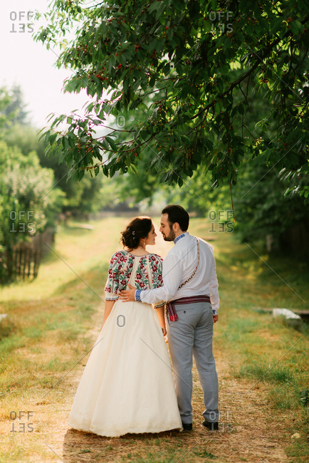 Portrait of Romanian bride and groom in traditional dress on farm