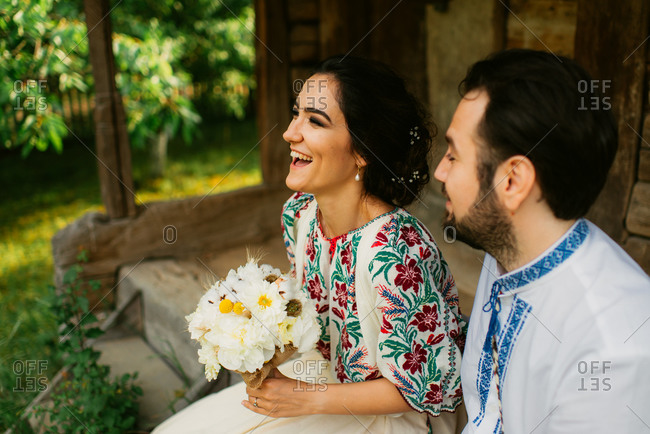 Romanian bride and groom in traditional folk costume talking together