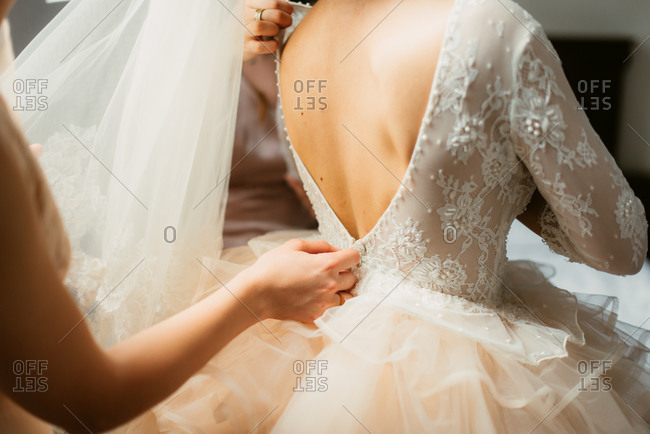 Woman zipping up bride's gown on her wedding day