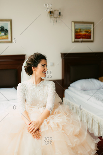 Beautiful bride sitting on bed in her wedding gown