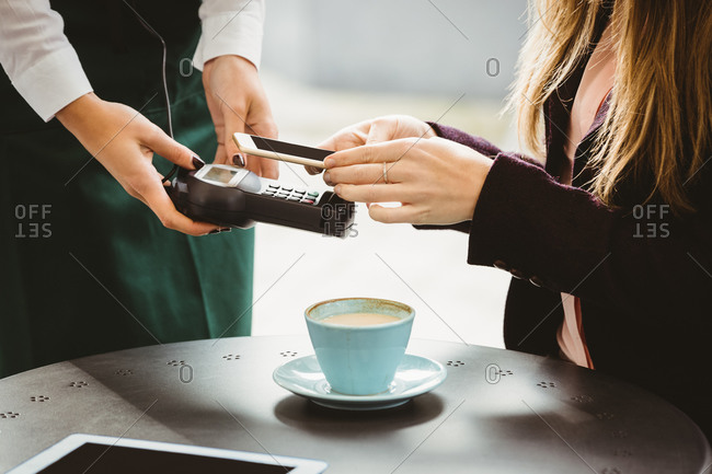 Woman paying with  smartphone in cafe