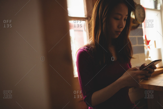 Brunette using her smartphone in the kitchen at home