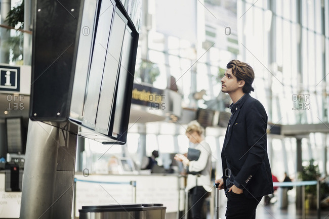 Businessman reading arrival departure board at airport