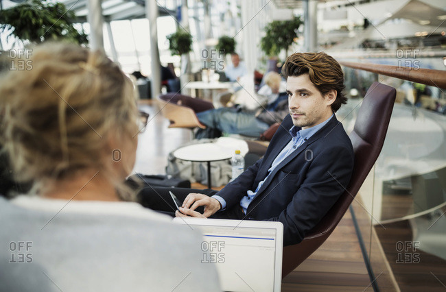 Businesspeople using technologies at lobby in airport