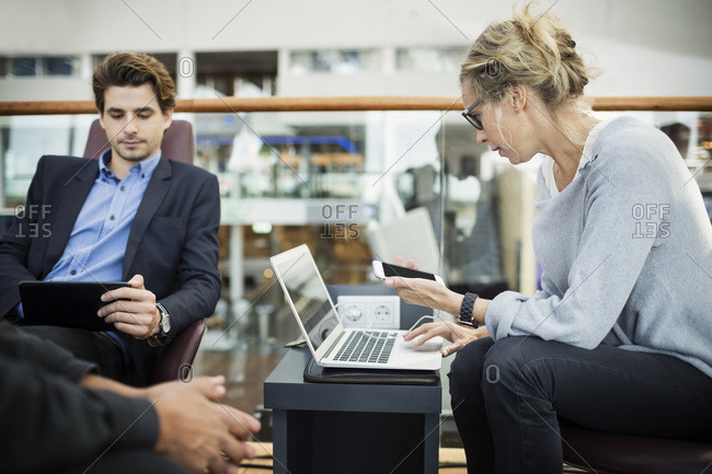 Businesspeople using technologies at airport lobby