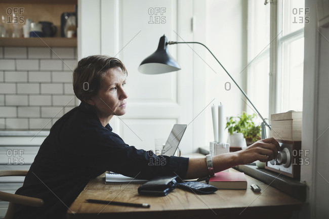 Side view of product designer adjusting radio at home office