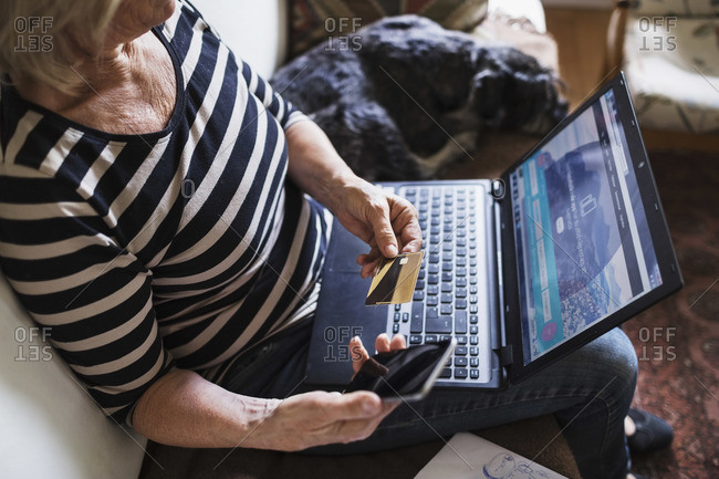 High angle view of senior woman with technologies and credit card sitting by dog on sofa