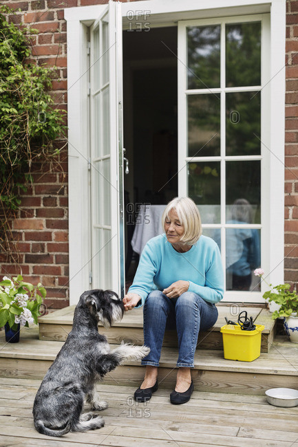 Senior woman sitting with dog at doorway