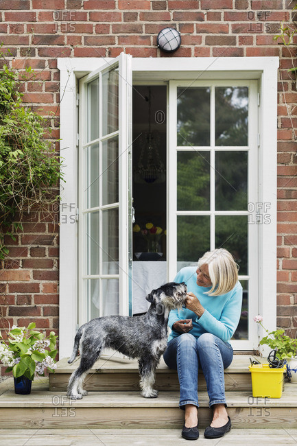 Happy senior woman with dog at house entrance