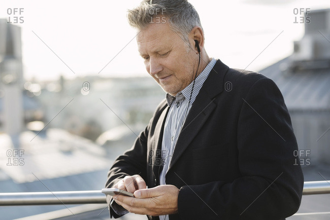 Mature businessman listening music through phone while standing at office