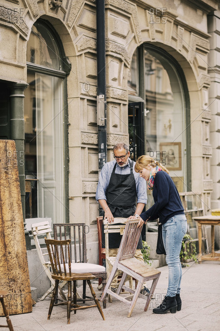 Retailer assisting customer in choosing chair outside antique shop