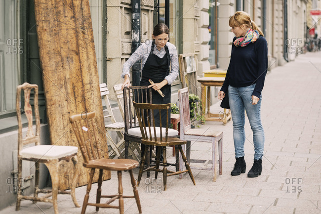 Female retailer showing antique chair to customer outside antique shop