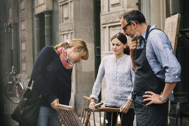 Female costumer choosing chair while retailers standing outside antique shop