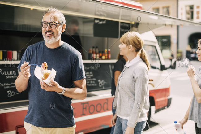 Mature man eating food while standing against truck at street