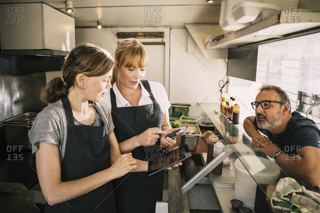 Female chefs with technologies while receiving order from man in food truck