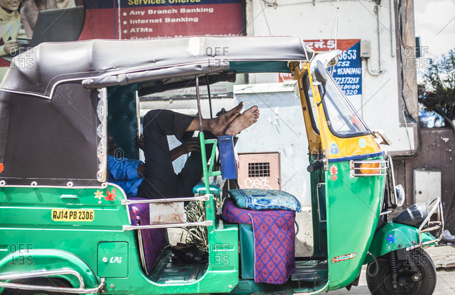 Jaipur, India - September 11, 2015: Driver resting his feet on the seat of his tuk tuk on a road in Jaipur, India