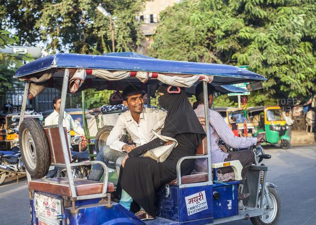 Jaipur, India - September 11, 2015: A man and woman riding on a tuk tuk through the streets of Jaipur, India