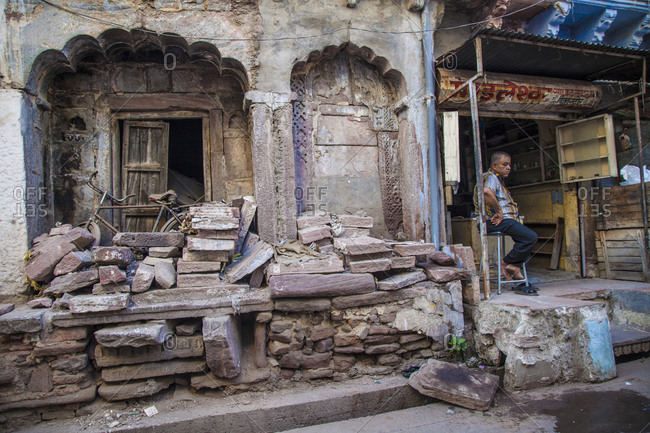 Rajasthan, India - September 12, 2015: Man sitting on a stool outside a rundown business in Jodhpur, India