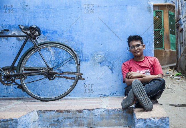 Rajasthan, India - September 12, 2015: Man sitting against a blue wall and a bicycle in the city of Jodhpur, India