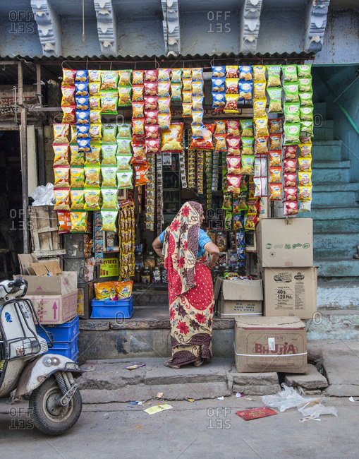 Rajasthan, India - September 12, 2015: Woman standing in front of a small market stall on a street in Jodhpur, India