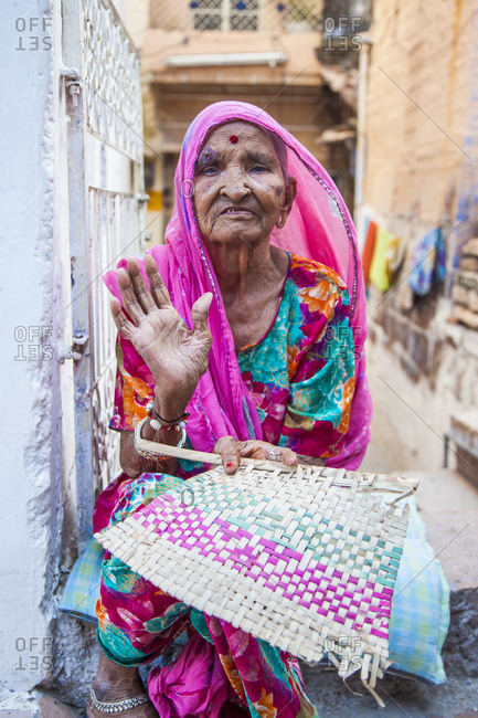 Rajasthan, India - September 12, 2015: Woman sitting in an alley in the city of Jodhpur, India