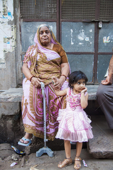 Rajasthan, India - September 12, 2015: Older woman sitting with young girl on a sidewalk in the city of Jodhpur, India
