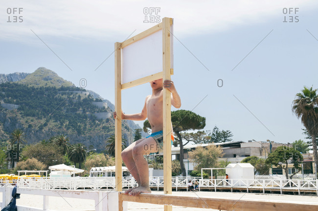Boy standing on a fence along a beach in Palermo, Sicily