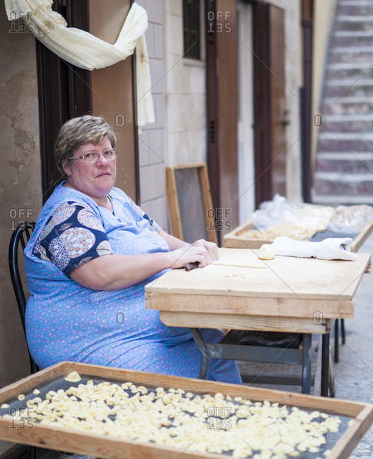 Puglia, Italy - May 14, 2015: Woman sitting outside hand rolling pasta in Puglia, Italy