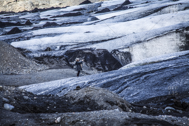 Woman taking a photograph of a glacier in Reykjavik, Iceland